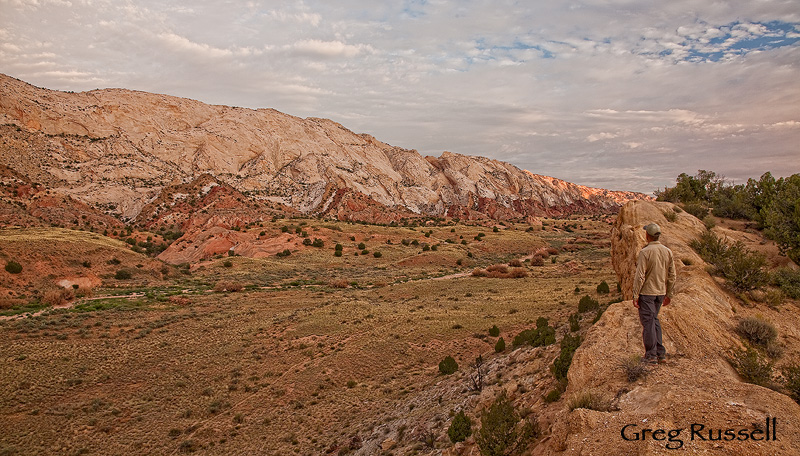 A hiker stands in Capitol Reef National Park in the early morning, just after dawn