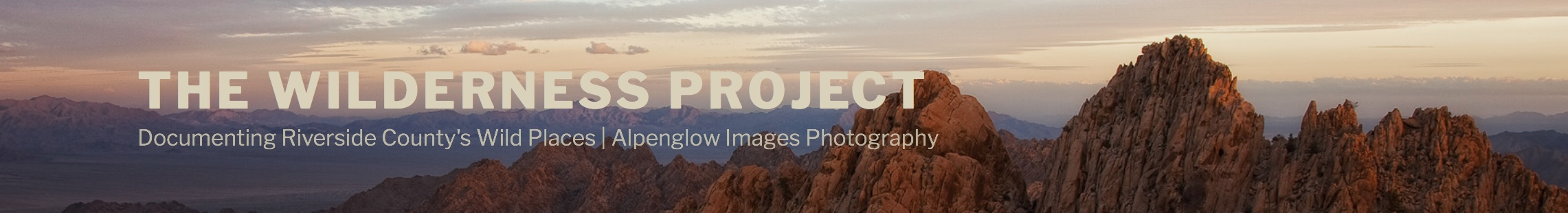panoramic image with text and colorful mountains at sunset