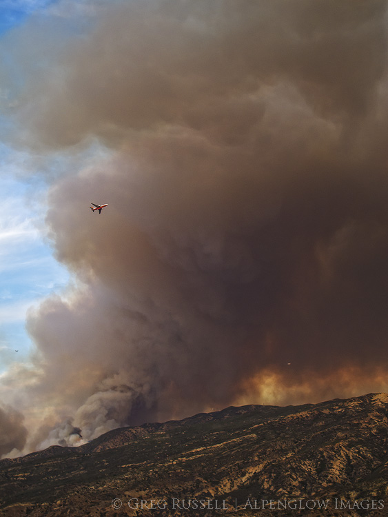 Photo of an air tanker flying by a large plume of smoke from the Canyon Fire in Orange County California, September 2017